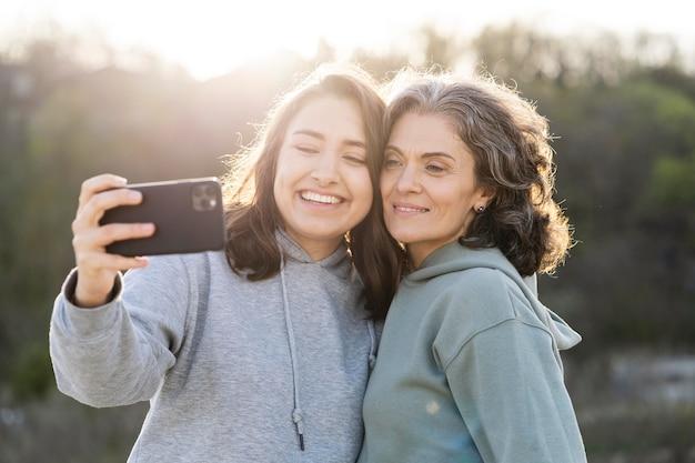 Filha sorridente tirando uma selfie com a mãe ao ar livre