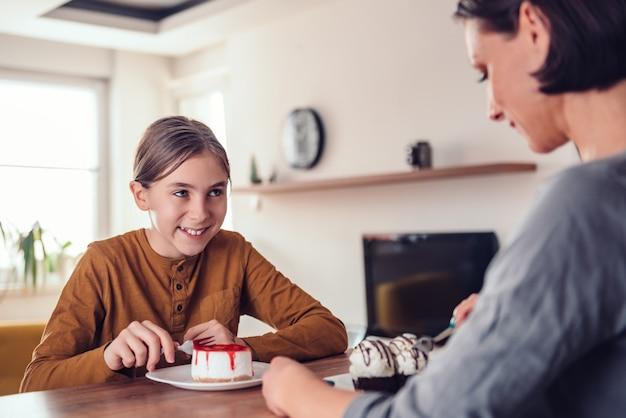 Filha, sorrindo e comendo bolo de queijo com a mãe