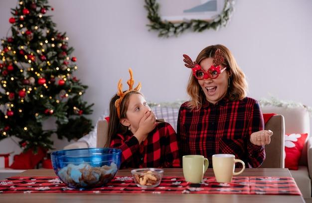 Filha surpresa, olhando para a mãe sentada à mesa, aproveitando o natal em casa