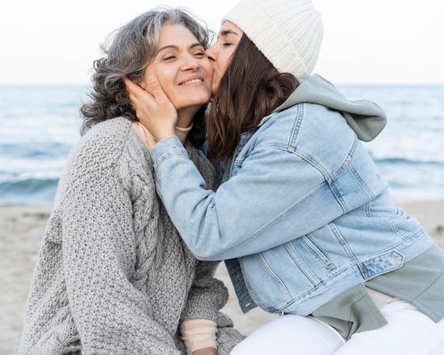 Filha tendo um momento de ternura com a mãe na praia