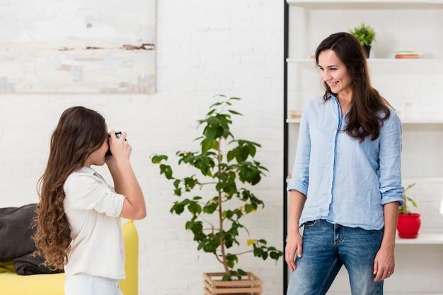 Filha tirando uma foto de sua mãe
