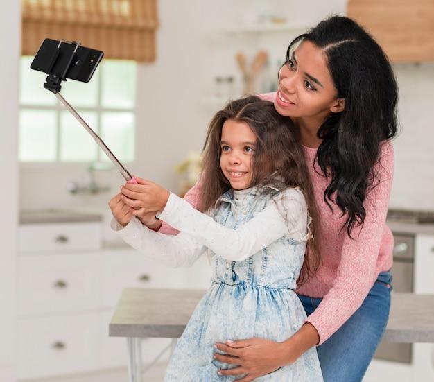 Filha tomando selfie com a mãe