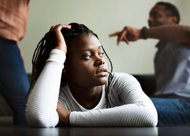 Filha tristemente sentada enquanto os pais brigam