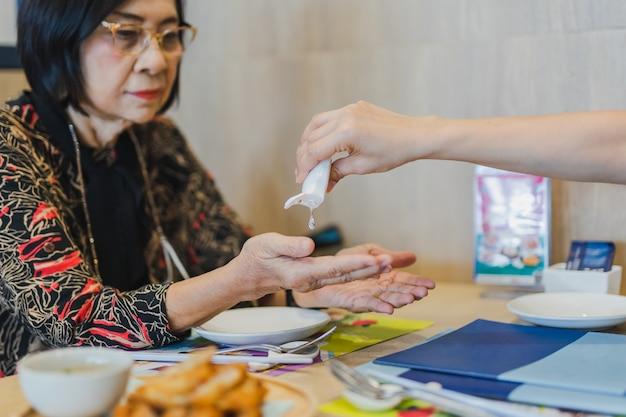 Filha usando álcool gel, limpando a mão da mãe sênior.