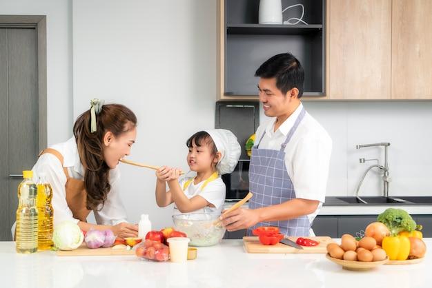 Filhas asiáticas dando salada para a mãe e o pai ficam de prontidão quando uma família cozinha