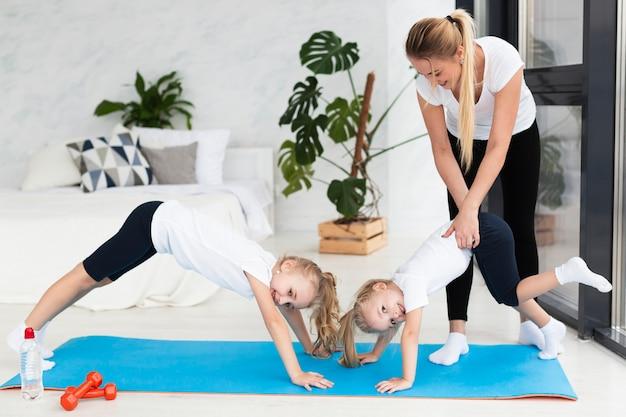Filhas de mãe ajudando a exercitar em casa