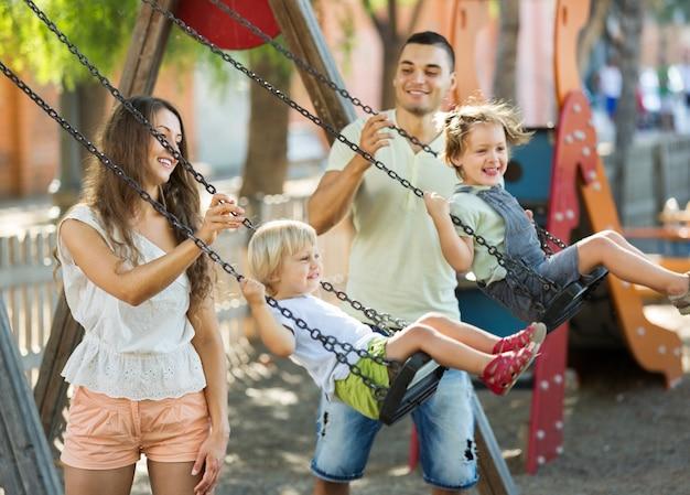 Filhas em baloiços com os pais