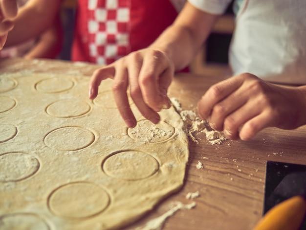 Filhas pequenas que cozinham na cozinha em casa todos junto. família feliz e conceito de estilo de vida.