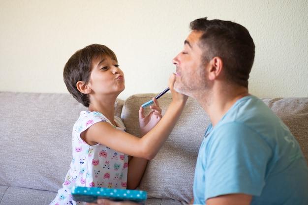 Filhinha bonita fazendo maquiagem para o pai