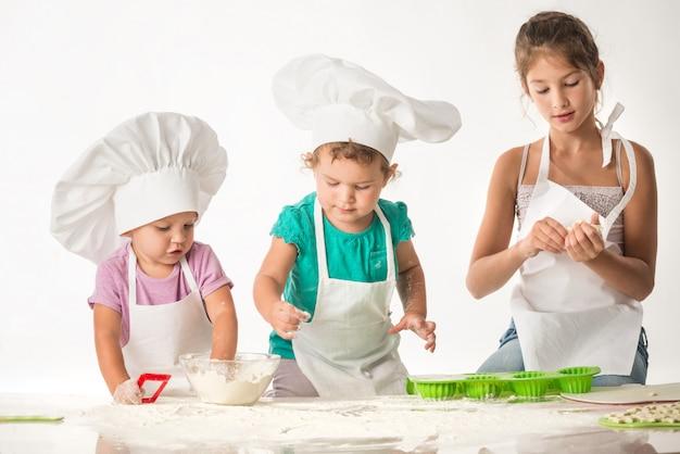 Filhinhos bonitos em um terno de cozinheiro cozinhar biscoitos