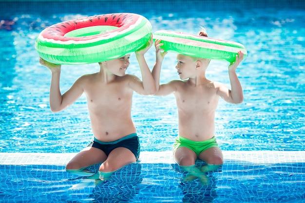 Filhinhos bonitos perto da piscina. crianças se divertindo no verão.