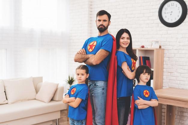 Filhinhos e jovens pais em ternos de super-heróis.