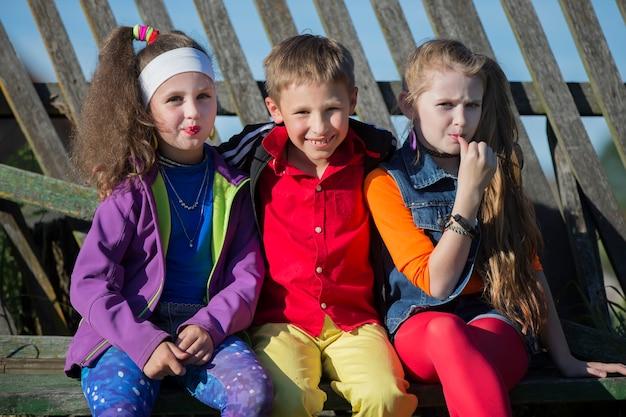 Filhinhos engraçados: meninas com maquiagem brilhante vestidas no estilo dos anos noventa e um menino de camisa vermelha estão sentados em um banco perto de uma cerca enviesada. crianças da aldeia russa.