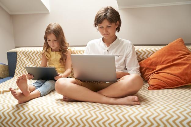 Filhinhos, irmão e irmã, sentados no sofá, usando laptop e tablet digital