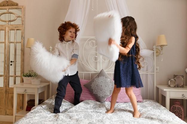 Filhinhos, menino e menina brincando com almofadas na cama.