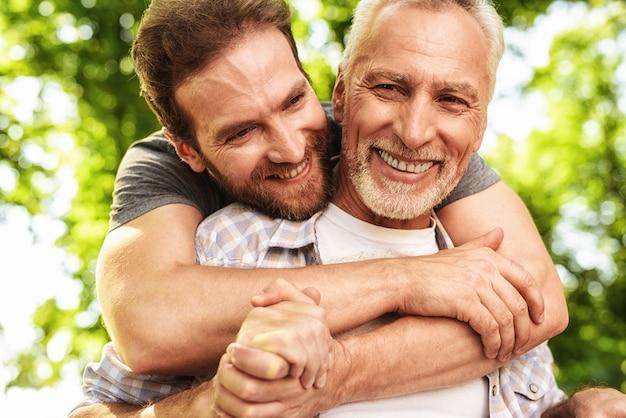 Filho abraça o velho. família caminhando no parque juntos.