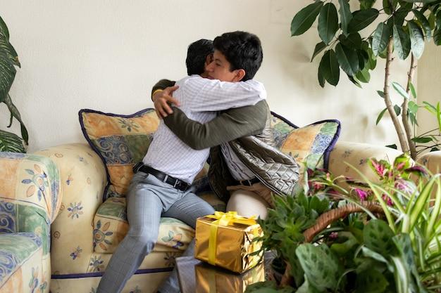 Filho abraçando seu pai enquanto lhe dava um presente