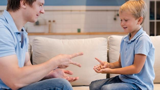 Filho adorável brincando com o pai de frente