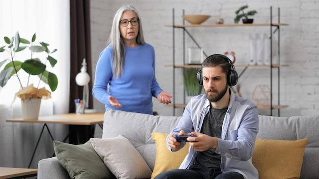Filho adulto jogando videogame em casa usando gamepads, ignorando a mãe sênior gritando com ele.