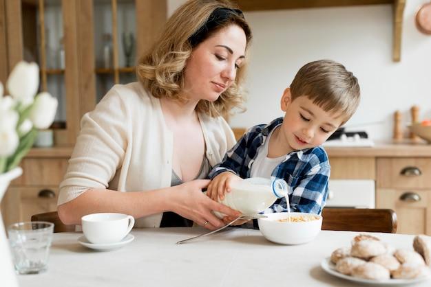 Filho, ajudando a mãe a derramar leite na tigela