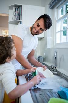Filho, ajudando o pai em lavar utensílios