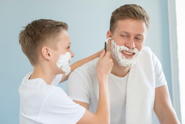 Filho ajudando seu pai a fazer a barba