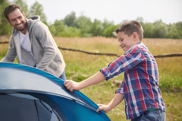 Filho ajudando seu pai no acampamento