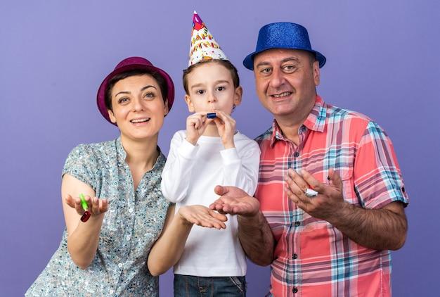Filho alegre com chapéu de festa soprando apito em pé com a mãe e o pai segurando apitos de festa isolados na parede roxa com espaço de cópia