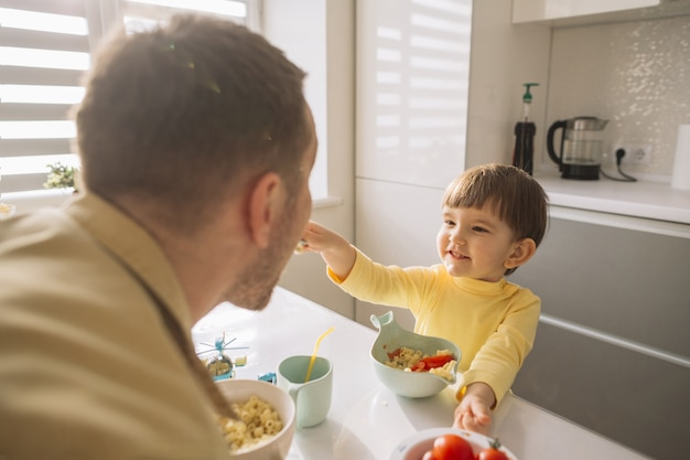 Filho, alimentando seu pai na cozinha