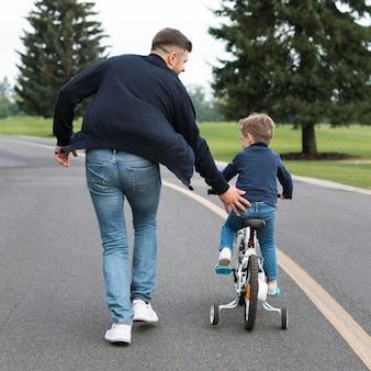 Filho andando de bicicleta no parque ao lado do pai por trás
