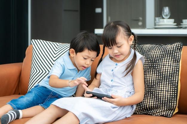Filho asiático fofo com um irmão usando um smartphone