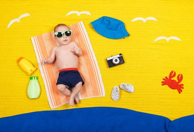 Filho bonito em calção de banho está deitado sobre uma toalha. férias de verão