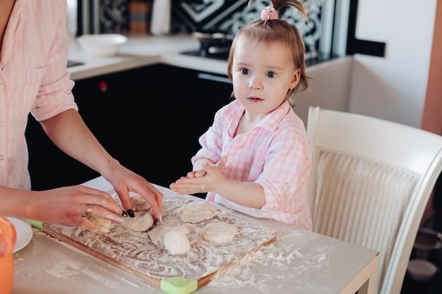 Filho bonito em farinha cozinhar junto com os pais na cozinha