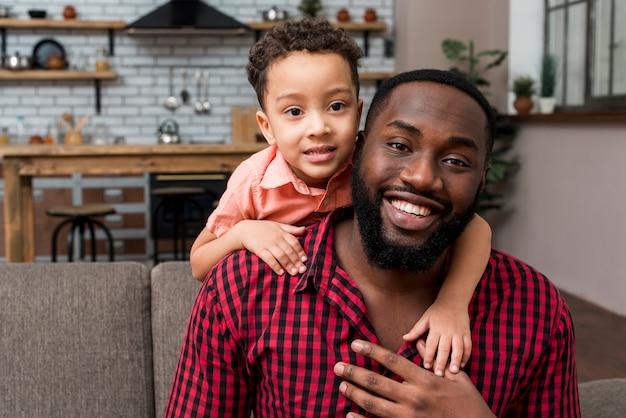 Filho bonito preto, abraçando o pai por trás