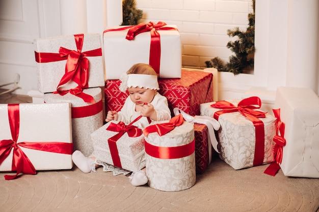Filho bonito vestido branco posando debaixo da árvore de natal.