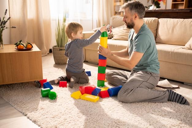 Filho brincando com cubos de brinquedo