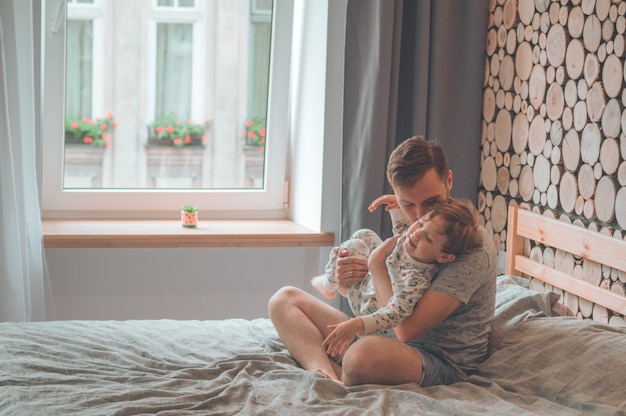 Filho brincando com o pai no sofá. família amorosa feliz