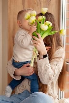 Filho dando flores para a mãe