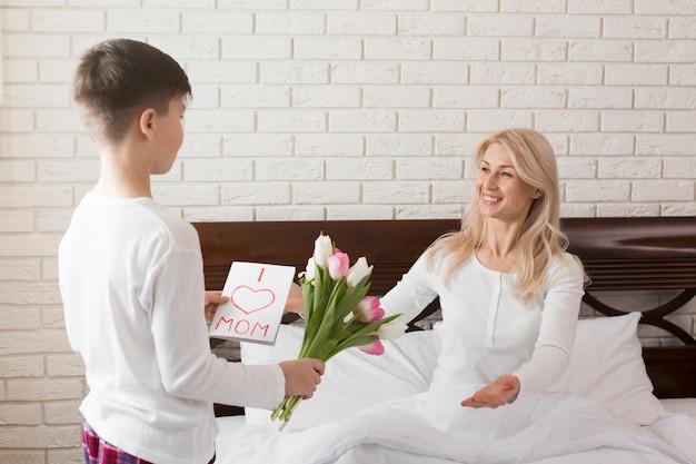 Filho dando flores para sua mãe