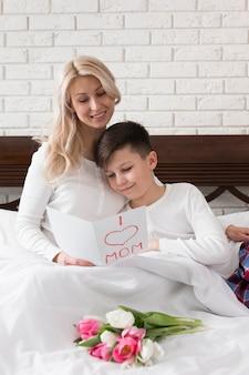 Filho de ângulo alto e mãe lendo filhos cartão