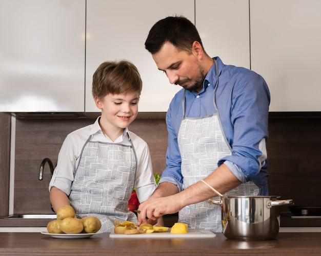 Filho de ângulo baixo, ajudando o pai a cozinhar
