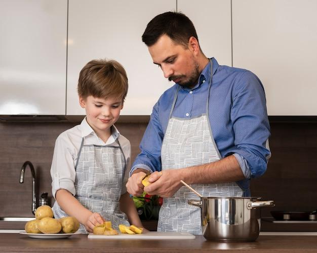 Filho de ângulo baixo, ajudando o pai durante o cozimento