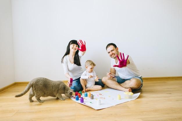 Filho de família feliz com os pais e um gato pintando um cartaz e outro com tintas