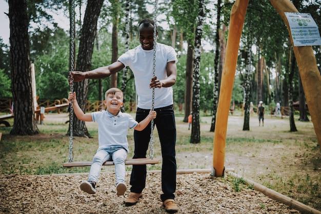 Filho de pai africano balançando filho adotado ri