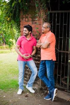 Filho de pai sênior indiano asiático posando para foto enquanto usava jeans e camiseta, contra uma parede de tijolo vermelho