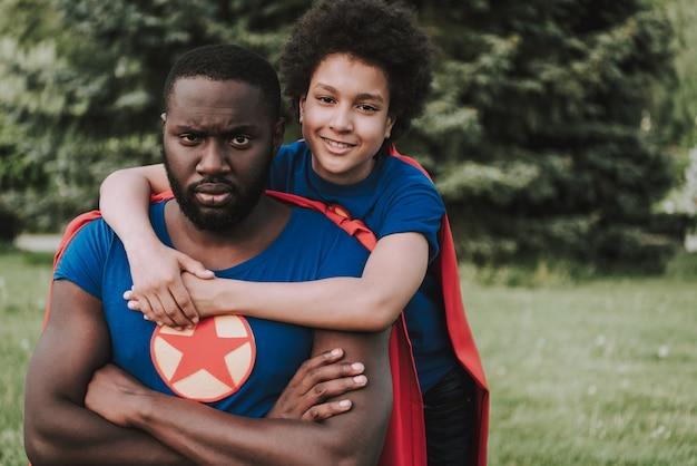 Filho de terno de super-herói abraça pai sério