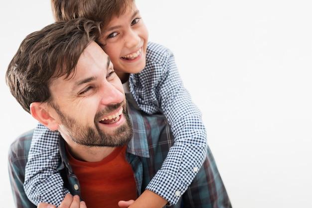 Filho de vista frontal, abraçando seu pai