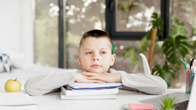 Filho de vista frontal, segurando sua cabeça em uma pilha de livros