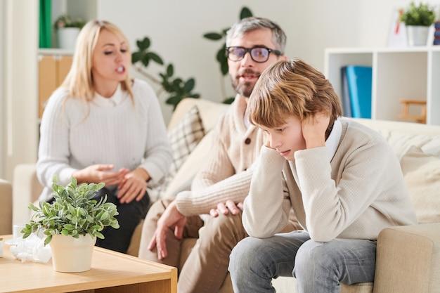 Filho deprimido, cobrindo as orelhas para evitar que os pais briguem