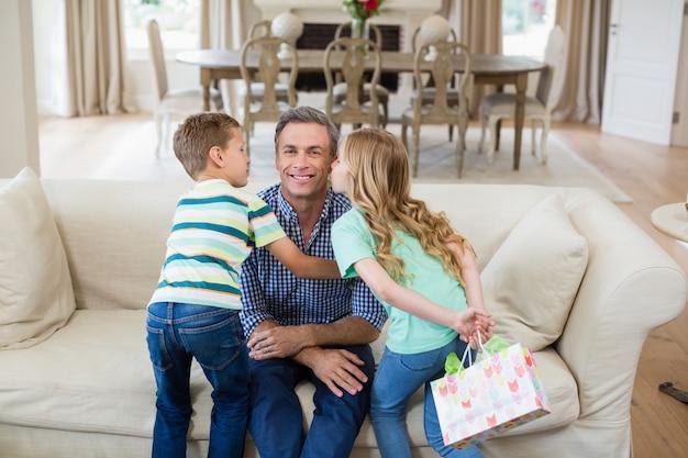 Filho e filha beijando seu pai na bochecha na sala de estar